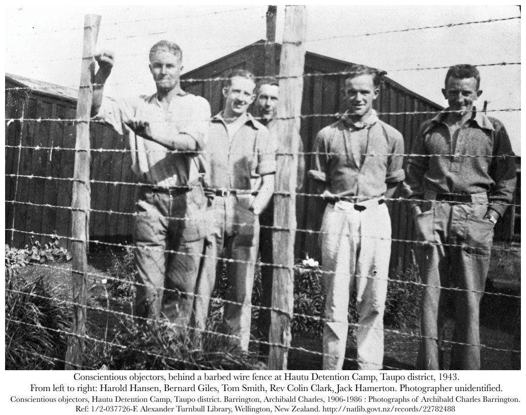 Conscientious objectors, behind a barbed wire fence at Hautu Detention Camp, Taupo district, New Zealand, 1943